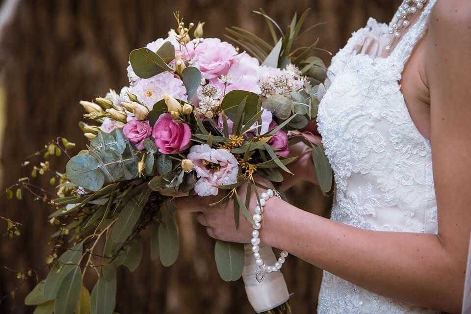 Menyasszonyi csokor a hozzáillő zöld levelekkel van körítve.